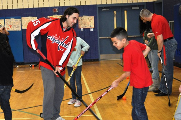 Washington Capitals forward Mathieu Perreault helps show a student at Kemp Mill Elementary School in Silver Spring, Md., how to stickhandle during Capitals Hockey School. 3/7/2012 (Photo Courtesy of Washington Capitals)