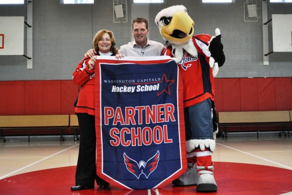 Washington Capitals assistant coach Calle Johansson, Capitals mascot Slapshot and Blessed Sacrament School principal Valerie Garcia pose with a Hockey School partner banner. Following a hockey clinic, the Capitals donated a set of street hockey equipment to the school. (Photo Courtesy of Washington Capitals)