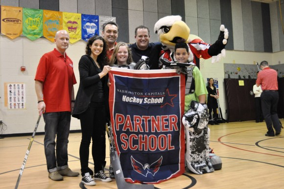 Washington Capitals assistant coach Blaine Forsythe, alumnus Nelson Burton and mascot Slapshot pose with Crestwood Elementary School students and staff following a Capitals Hockey School assembly. (Photo courtesy of Washington Capitals).