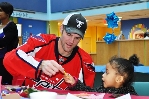 Washington Capitals defenseman Tom Poti works on an arts and crafts project with a child at Children's National Medical Center in Washington, D.C. during a Feb. 15 visit. (Photo Courtesy of Washington Capitals)