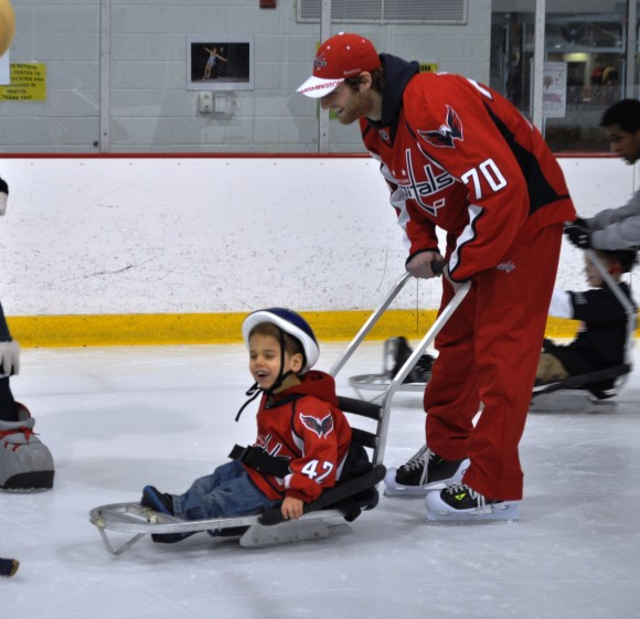 Washington Capitals goaltender Braden Holtby pushes the sled of a child trying out sled hockey during a Dreams for Kids Extreme Recess clinic at Kettler Capitals Iceplex on Feb. 8. (Photo Courtesy of Washington Capitals)