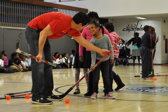 Washington Capitals alumnus Alan May instructs a student on stickhandling during a Hockey School assembly at Thurgood Marshall Elementary School in Washington, D.C. The event was held in conjunction with the Capitals celebration of Hockey is for Everyone™ Month, a league wide initiative that offers children of all backgrounds opportunities to play hockey. (Photo Courtesy of Washington Capitals)