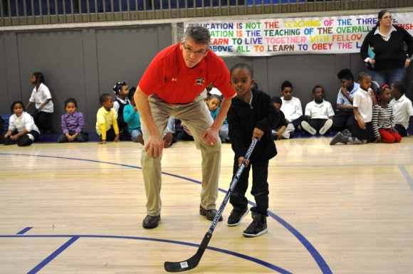 Washington Capitals alumnus Paul Mulvey advises a Thurgood Marshall Elementary School student on passing during a Hockey School program at the school on Feb. 11. During the assembly alumnus Alan May and Mulvey guided the students through several drills focusing on stickhandling, passing and shooting prior to inviting them to demonstrate what they learned. (Photo Courtesy of Washington Capitals)