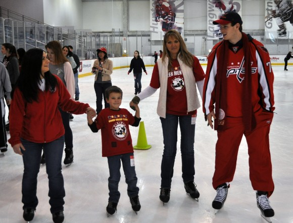 Washington Capitals defenseman John Carlson skates with children and adults assisted by the Tragedy Assistance Program for Survivors during a skating party at Kettler Capitals Iceplex in Arlington, Va. For the second-consecutive season, TAPS is the beneficiary of Courage Caps, team-issued branded hats and T-shirts that will go on sale beginning March 10, when the Capitals host the New York Rangers. (Photo Courtesy of Washington Capitals)