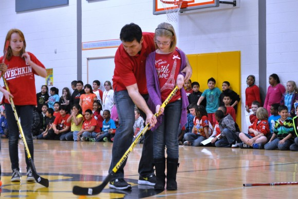 Washington Capitals alumnus Alan May instructs a student on stickhandling during a Washington Capitals Hockey School at Manassas Park Elementary School on April 5. The visit marked the team's fourteenth assembly of the academic year. (Photo Courtesy of Washington Capitals)