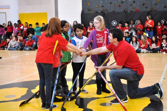 Washington Capitals alumnus Alan May leads his team in a chant prior to playing in a scrimmage against Slapshot's boys team. Hockey School is a free instructional and interactive program that aims to expose students to floor hockey while teaching proper technique. (Photo Courtesy of Washington Capitals)