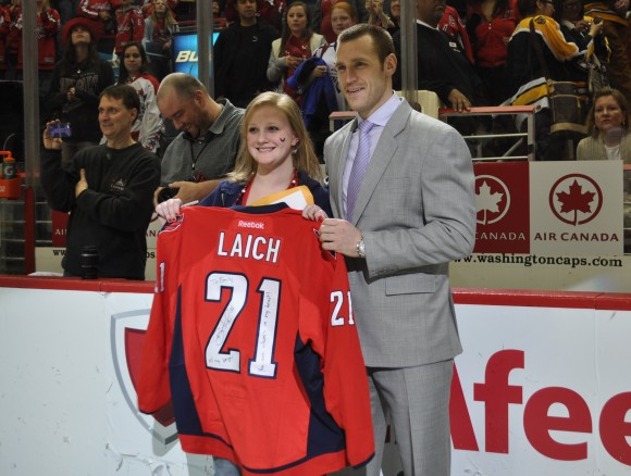 During the Capitals Fan Appreciation Night Jersey Off Our Backs ceremony, Capitals forward Brooks Laich presents Emily, 17, with his jersey. Through the Capitals and Make-A-Wish® Mid-Atlantic, Emily was able to meet Laich. (Photo Courtesy of Washington Capitals)