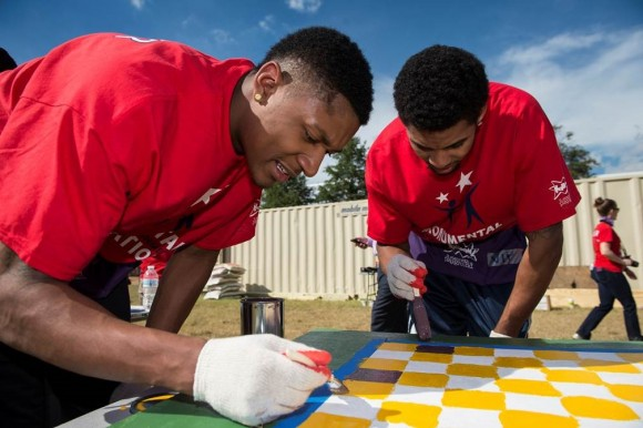 Washington Wizards players Bradley Beal (L) and Glenn Rice, Jr. help paint a table near the playground at Eagle Academy Public Charter School in Washington, D.C. Earlier this summer, Beal assisted the students with the design of the playground. The build is the first joint effort by KaBOOM! and Monumental Sports & Entertainment Foundation. (Photo Courtesy of Monumental Sports)