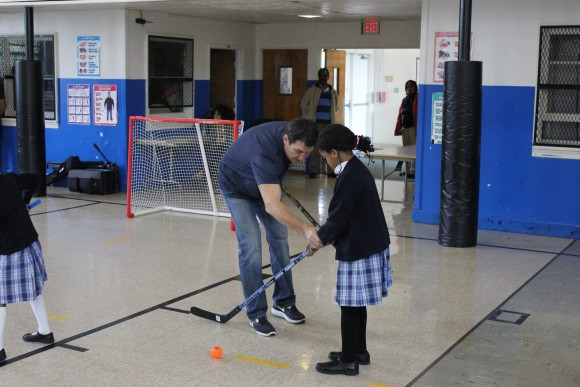 Washington Capitals alumnus Alan May instructs a St. Mary's School student on stickhandling during a Hockey School assembly on Oct. 23. Hockey School is a free program, designed to be both instructional and interactive, with the goal of exposing students to floor hockey while teaching proper technique. (Photo Courtesy of Washington Capitals)