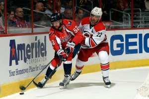 Mike Green battles with the puck against Manny Malholtra. (Photo by Patrick McDermott/NHLI via Getty Images)