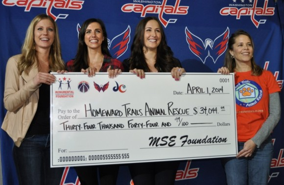 Carmen Brouwer, Courtney Parrie and Mandy Alzner present a $34,044.99 check to Homeward Trails representative Sue Bell at the Washington Capitals game on April 1. The funds were donated by Monumental Sports & Entertainment Foundation and were raised through the sale of the 2014 Caps Canine Calendars. (Photo Courtesy of MSEF)