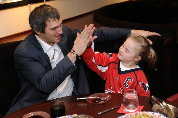 Washington Capitals captain high fives 10-year old Ann as forward Nicklas Backstrom signs her jersey. As part of her date with Ovechkin Ann met numerous Capitals players in the locker room, including defenseman Mike Green (center). (Photo Courtesy of Washington Capitals)