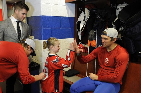 "Washington Capitals captain Alex Ovechkin poses with his ""date,"" 10-year-old Ann, following the Capitals game versus the Carolina Hurricanes on Oct. 5. Ann asked Ovechkin on a date during a skate he hosted at Kettler Capitals Iceplex on Sept. 11 and Ovechkin surprised her by granting her request during the Capitals' final preseason game. (Photo Courtesy of Washington Capitals)"