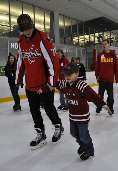 Washington Capitals defenseman John Carlson skates with a child who has found healing through TAPS. The Washington Capitals hosted more than 150 children and adults who are assisted by the program for a skating party at Kettler Capitals Iceplex on Feb. 24 to launch the 2014-15 Courage Caps campaign. (Photo Courtesy of Washington Capitals)