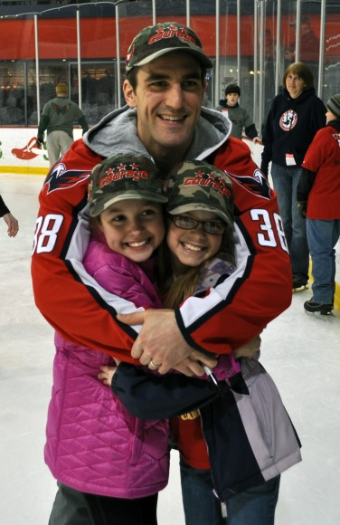 Washington Capitals defenseman Jack Hillen poses with young fans at a skating party to benefit children and adults who have found healing through TAPS. Hillen and the children are wearing the Washington Capitals team-branded Courage Caps. The Courage Caps campaign is sponsored by Telos Corporation, and 100% of the proceeds raised through the sale of Courage Caps will go to TAPS.  (Photo Courtesy of Washington Capitals)