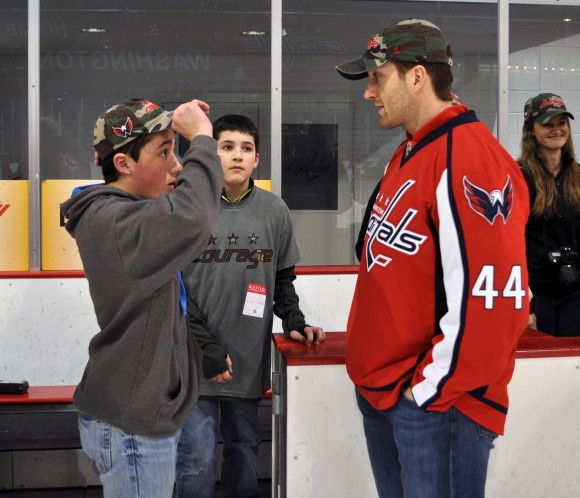 Washington Capitals defenseman Brooks Orpik chats with young fans at a skating party to benefit children and adults who have found healing through TAPS. Orpik and the children are wearing the Washington Capitals team-branded Courage Caps. The Courage Caps campaign is sponsored by Telos Corporation, and 100% of the proceeds raised through the sale of Courage Caps will go to TAPS. (Photo Courtesy of Washington Capitals)